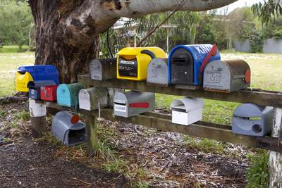 Colourful mailboxes at a road junction in Pohara on South Island New Zealand