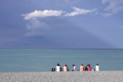 A group of people sit on Kaikoura beach, looking for whales in the Pacific Ocean on South Island in New Zealand