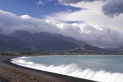 Clouds gather over the Kaikoura range of mountains while surf crashes in on the shingle beach on South Island in New Zealand