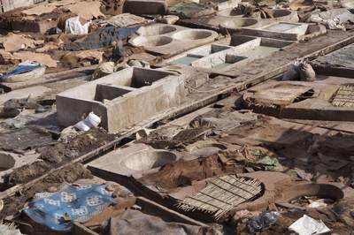 The tanneries just off of Rue Bab Debbagh in the Northern Medina showing the dye pits, many full of poisonous substances with two men working in the city of Marrakech Marrakesh in Morocco in Africa