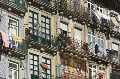 Portuguese flags and washing hung out on tiled buildings along Rua Dr Barbosa de Castro in Porto, Northern Portugal, Europe