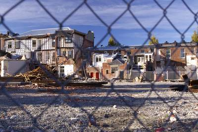 Homes destroyed by the earthquake on the 22 February 2011 which killed 185 people with access denied by a wire fence for safety reasons in Christchurch on South Island New Zealand