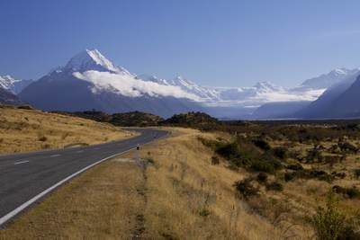 The road to Mount Cook -SH80 - heading towards Mount Cook village alongside the shoreline of Lake Pukaki in the Mount Cook National Park with the snow covered peak of Mount Cook in the distance on South Island in New Zealand