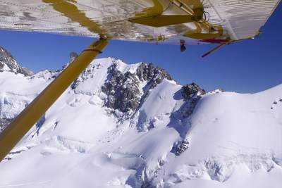 Aerial view of the mountains in the Mount Cook National Park from under the wing of a Pilatus Porter PC6 plane on South Island in New Zealand
