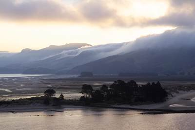 Evening mist rolls over the hills, viewed across the Otago harbour in Dunedin on South Island in New Zealand