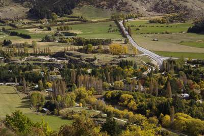 View down onto State Highway 6 out of Queenstown with the colours of early autumn developing on South Island in New Zealand