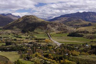 View across the valley towards Queenstown, Lake Wakatipu and the Richardson Mountains with the colours of early autumn developing on South Island in New Zealand