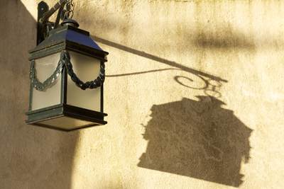Wrought iron lamp casts a shadow in the evening light in Pé da Serra, Colares in Portugal Europe