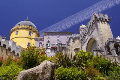 Blue sky with a vapour trail behind the brightly coloured architecture of Pena National Palace in Sintra in Portugal, Europe
