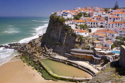 View down onto the terracotta tiled roofs of the seaside town of Azenhas do Mar with seawater lido on the beach in Colares, Portugal Europe