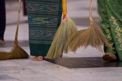 It is considered a good deed to help sweep the Shwedagon Pagoda marble flooring - at around 6pm many people (women and men work separately) sweep the marble floor in a line working in a clockwise direction around the central stupa of the complex in Yangon (Rangoon) in Myanmar (Burma)