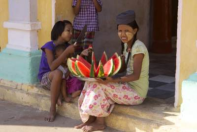 Young women sell sliced watermelons for refreshment within the Shwezigon Pagoda complex, built as the most important reliquary shrine in Bagan for King Anawarahta in Myanmar (Burma)