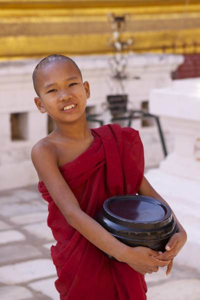 Burmese Novice monk in traditional dark red robes with his alms bowl in the Shwezigon Pagoda complex, built as the most important reliquary shrine in Bagan for King Anawarahta in Myanmar (Burma)