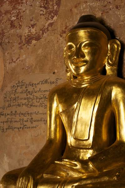 Seated golden Buddha within the Sulamani Pahto (Sulamani Guphaya) temple with Burmese writings on the wall behind in Bagan in Myanmar (Burma)