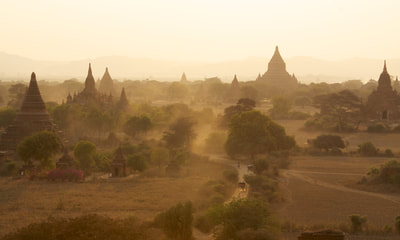 View across the temples on the plains of Bagan, viewed from the terraces of the Shwesandaw Paya temple in late afternoon and with dust raised by horse and carts in Bagan in Myanmar (Burma)