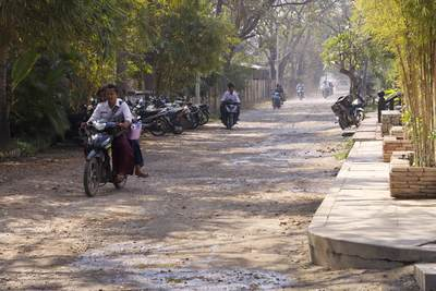 63rd Street in Mandalay - an unsurfaced road with local people riding to work on mopeds in Myanmar (Burma)