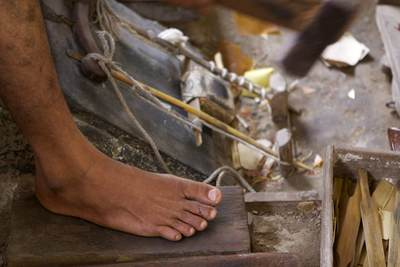 A man operates a machine by foot pedal, used in the process of gold beating at the King Galon gold workshop in Mandalay in Myanmar (Burma)