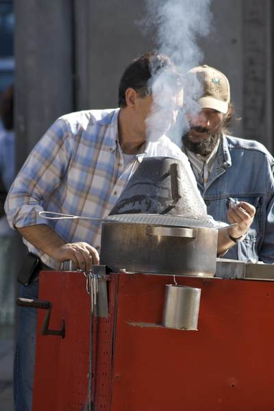 Chestnut seller in a checked shirt gives a sample to a passer-by with a baseball cap with rising smoke from his red stove in Porto, Portugal Europe