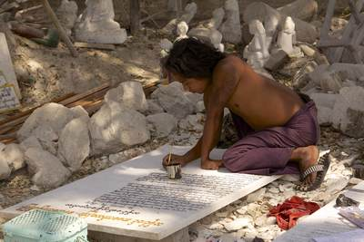 A man fills in engraved lettering with paint in a marble workshop in Mandalay in Myanmar (Burma)