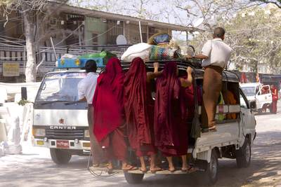 Three monks are transported on the back of a crowded minibus, along with goods for sale in the market in Mandaly in Myanmar (Burma)