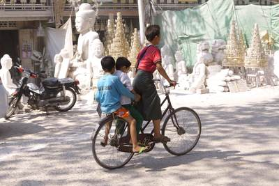 Three boys share a bicycle and ride along the Saigang-Mandalay Road in Myanmar (Burma)