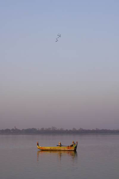 A flock of birds fly above a boat on the Taungthaman Lake near the town of Amarapura in Myanmar (Burma)