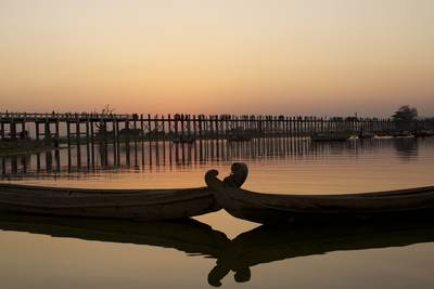The sun sets behind the U Bein bridge and two moored boats - the longest teak bridge in the world, crossing Taungthaman Lake near the town of Amarapura in Myanmar (Burma)