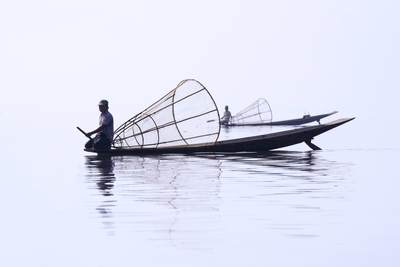 Inle Lake fishermen with bamboo fishing baskets in the early morning mist, traditional 'leg rowers' only found in Inle Lake in Myanmar (Burma)