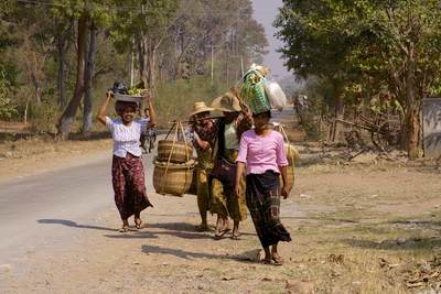 Women carry goods purchased from the local market in bags and containers on their heads and in large baskets to the village of Khaung Daing in Myanmar (Burma)