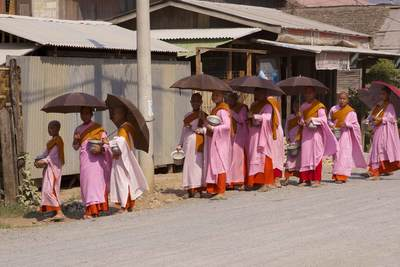 A queue of Novice monks wait to collects alms at lunchtime in the town of Nyaung Shwe, on the shores of Inle Lake in Myanmar (Burma)