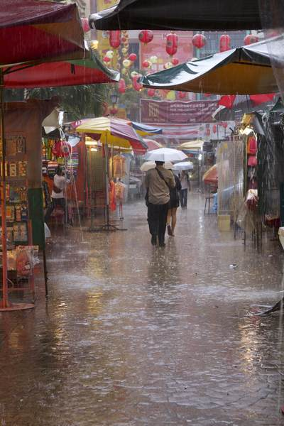 A seasonal monsoon lasting about an hour, in Petaling Street (a.k.a Jalan Petaling) in Chinatown with covered market stalls in Kuala Lumpur in Malaysia