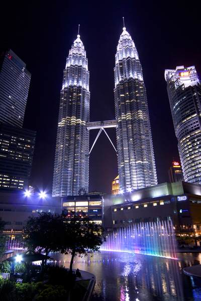 The twin Petronas Towers (Menara Petronas/ Menara Berkembar Petronas) rising above the Suria KLCC Mall at their base,  HQ of the Petronas oil company, still the tallest twin towers in the world, at night with the musically synchronised fountains of Lake Symphony in the foreground in Kuala Lumpur in Malaysia