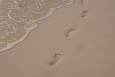 Footprints in the sand on a beach on the island of Besar (Pulau Perhentian) in the Perhentian islands in Malaysia