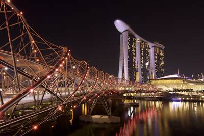 View of the Marina Bay Sands hotel along with the 'Helix' bridge in the foreground  floodlit at night in Singapore