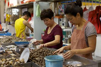 Two women pot up shell fish for customers on a stall in the Tekka Centre  located in Little India in Singapore