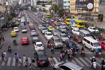 Motorbikes and cars wait at a pedestrian crossing at the junction of Thanon Asok Montri road with Sukhumvit road in central Bangkok in Thailand