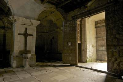 Entrance leading to the interior of Santo Estevo medieval church with large wooden cross, ornately carved double wooden doors and a flag stone floor near Ourense, Galicia in Spain in Europe