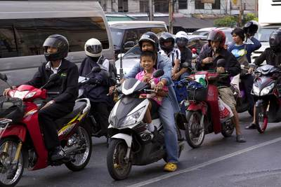 A man and boy riding on the same moped, wait in a queue of mopeds for the lights to change at the pedestrian crossing at the junction of Thanon Asok Montri road with Sukhumvit road in central Bangkok in Thailand