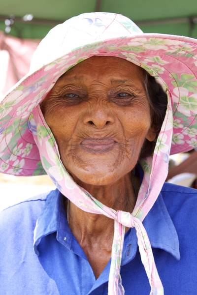 The face of an elderly Thai lady selling salt on a roadside stall outside Bangkok in Thailand