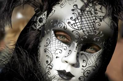 A woman wears an ornate silver Venetian mask at Carnival Carnevale in Venice in Italy, Europe
