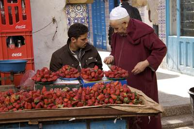 Young male strawberry seller sells strawberries to an old man wearing a traditional jellaba and skull cap on a paved side road in the Northern Medina of Essaouira with cobalt blue shuttered stalls in Morocco in Africa