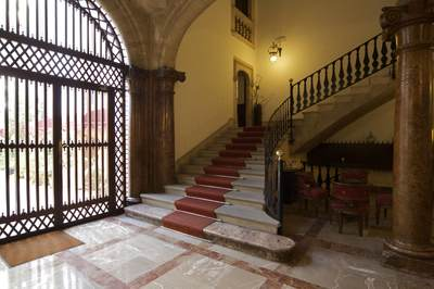 Entrance hallway of Hotel Born, a seventeenth century mansion in Palma with sweeping staircase, stone vaulted ceiling, marble flooring and wrought iron balustrade and gate to the inner courtyard, in Majorca Mallorca part of the Balearics in Spain Europe