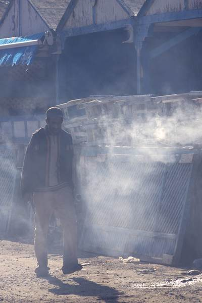 Middle aged man walks in the late afternoon sun through smoke from the seafood grill stalls in Essaouira in Morocco