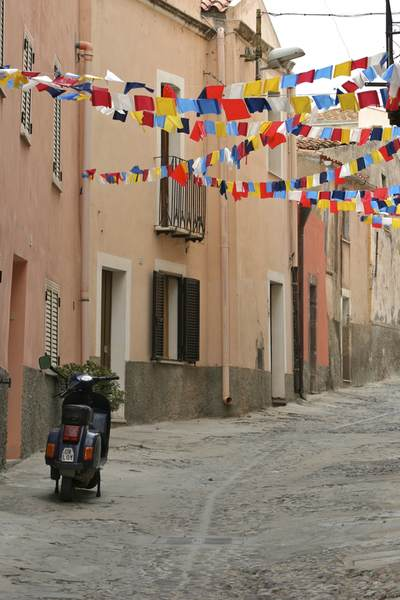 Steep cobbled street with peach coloured terraced houses  with wrought iron balconies with brightly coloured pennant flags and a moped parked in the road in the town of Bosa on Sardinia, Italy Europe