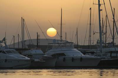Sunset over yachts and motor boats moored in the Alghero marina in Sardinia, Italy Europe