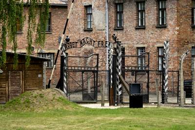 Gate to the entrance of Auschwitz 1 concentration camp with original  metal signage 'Arbeit Macht Frei'  (Work makes you free) and raised barrier with brick building blocks' near Krakow Crakow in Poland Europe