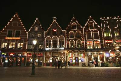 Buildings - mainly restaurants - covered in fairy lights on the Northern side of the cobbled Markt with Christmas decorations with Christmas shoppers in Brugges, Bruge, West-Vlaanderen in Belgium Europe