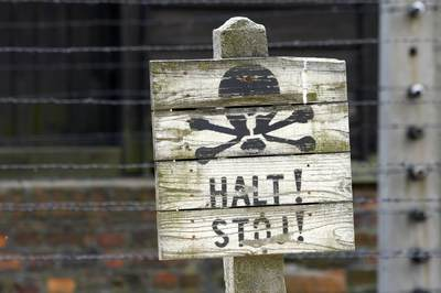 Wooden halt sign with skull and crossbones in front of barbed wire fence with concrete pillars surrounding one of the compounds in Auschwitz 1 concentration camp near Krakow Crakow in Poland Europe