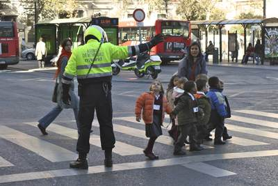 A 'Agent de Movilidad' (mobility Police Officer) assists a group of 8 school children with an adult to cross a busy road on the crossing with many buses and passers by, on Calle de Atocha, Madrid in Spain, Europe