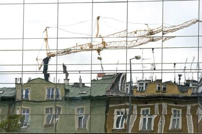 Reflections of cranes in glass windows of modern buildings and old buildings in the Ghetto district of Krakow Cracow in Poland Europe